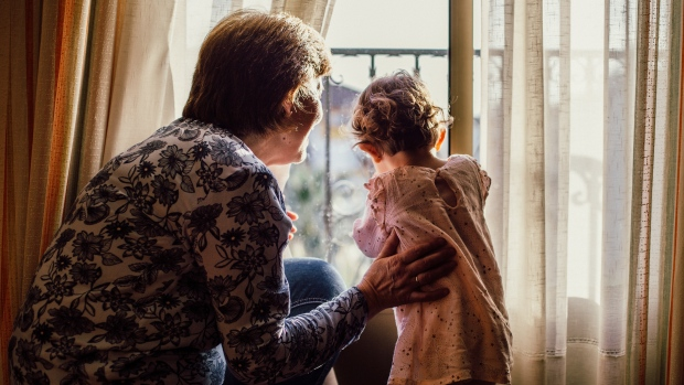 Woman, grandparent with child looking out window. (Pexels/Juan Pablo Serrano Arenas)