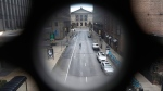 FILE - In this March 23, 2020 file photo, a man walks across a nearly empty Adams Street near The Art Institute of Chicago, in Chicago, on the first work day since Illinois Gov. J.B. Pritzker gave a shelter in place order last week. (AP / Charles Rex Arbogast, File)