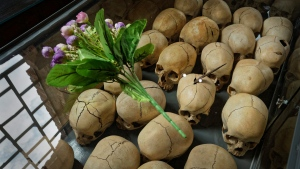 Flowers are laid on top of a glass case containing the skulls of some of those who were slaughtered as they sought refuge in a church in Ntarama, Rwanda, on April 5, 2019. (Ben Curtis / AP)
