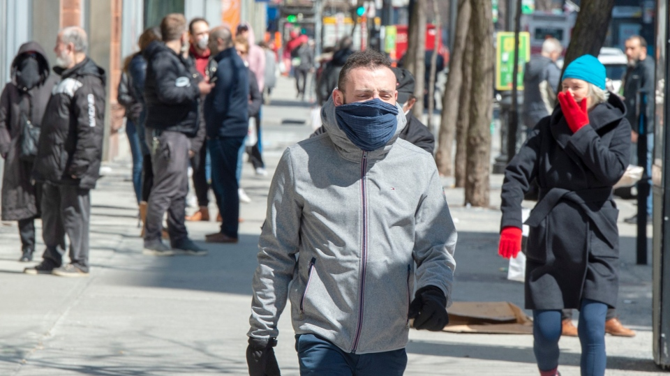 Pedestrians wear makeshift face coverings as they walk down St. Catherine street Monday April 6, 2020 in Montreal.THE CANADIAN PRESS/Ryan Remiorz