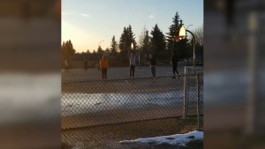 People playing basketball at the outdoor courts at Airdrie's Muriel Clayton Middle School on April 6, 2020