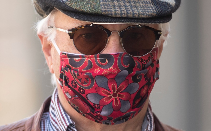 Paul Pedersen wears a mask quilted by his wife as he walks along the street in Ottawa, Monday April 6, 2020. THE CANADIAN PRESS/Adrian Wyld