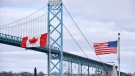 Canadian and American flags fly near the Ambassador Bridge at the Canada/USA border crossing in Windsor, Ont. on March 21, 2020. THE CANADIAN PRESS/Rob Gurdebeke