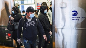Subway riders, wearing personal protective equipment due to COVID-19 concerns, step off a train, Tuesday, April 7, 2020, in New York. (AP Photo/John Minchillo)