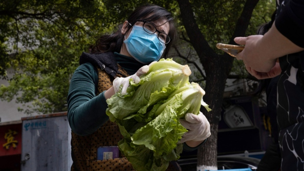 Handing vegetables to a resident outside a community in Wuhan, China, on April 6, 2020. (Ng Han Guan / AP)