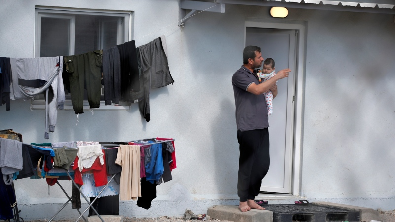 A migrant holds a baby outside a container house during a quarantine against coronavirus at a refugee camp in Ritsona about 80 kilometers (50 miles) north of Athens, Thursday, April 2, 2020. (AP Photo/Thanassis Stavrakis)
