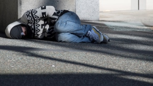 A homeless man sleeps on the sidewalk in downtown Vancouver, Monday, April 6, 2020. THE CANADIAN PRESS/Jonathan Hayward