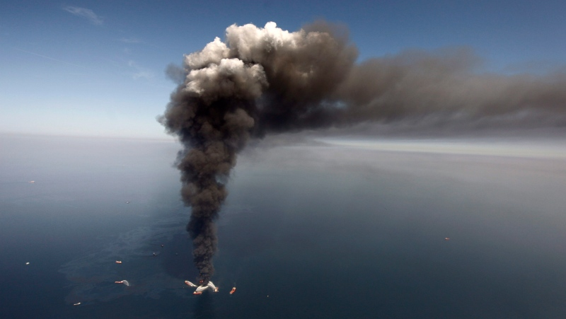 In this April 2010 file photo, oil can be seen in the Gulf of Mexico, more than 50 miles southeast of Venice on Louisiana's tip, as a large plume of smoke rises from fires on BP's Deepwater Horizon offshore oil rig. (AP Photo/Gerald Herbert, File)