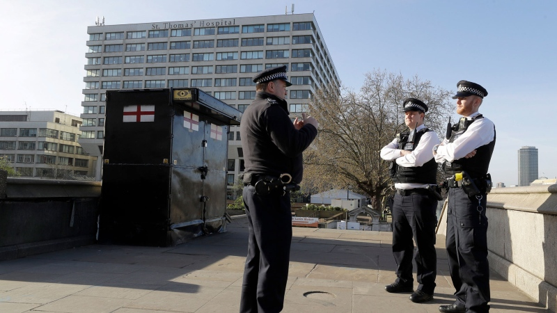Police officers stand outside St Thomas' Hospital in central London as British Prime Minister Boris Johnson was moved to intensive care after his coronavirus symptoms worsened in London, Tuesday, April 7, 2020. (AP / Kirsty Wigglesworth)