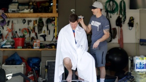 Mike Swyt, left, gets a haircut in his garage from his brother-in-law, Ryan Nolan, because barber shops are closed due to the coronavirus outbreak Sunday, April 5, 2020, in Nolensville, Tenn. (AP Photo/Mark Humphrey)