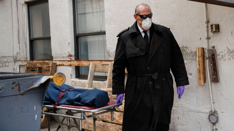 Funeral director Tom Cheeseman collects a body from a nursing home, Friday, April 3, 2020, in the Brooklyn borough of New York. He wears the shades for every call, even when it's gray and rainy. He likes that light seeps into his peripheral vision, no matter how dreary. (AP / John Minchillo)