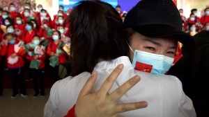 A medical worker from China's Jilin Province reacts as she prepares to return home at Wuhan Tianhe International Airport in Wuhan in central China's Hubei Province, Wednesday, April 8, 2020.  (AP Photo/Ng Han Guan)