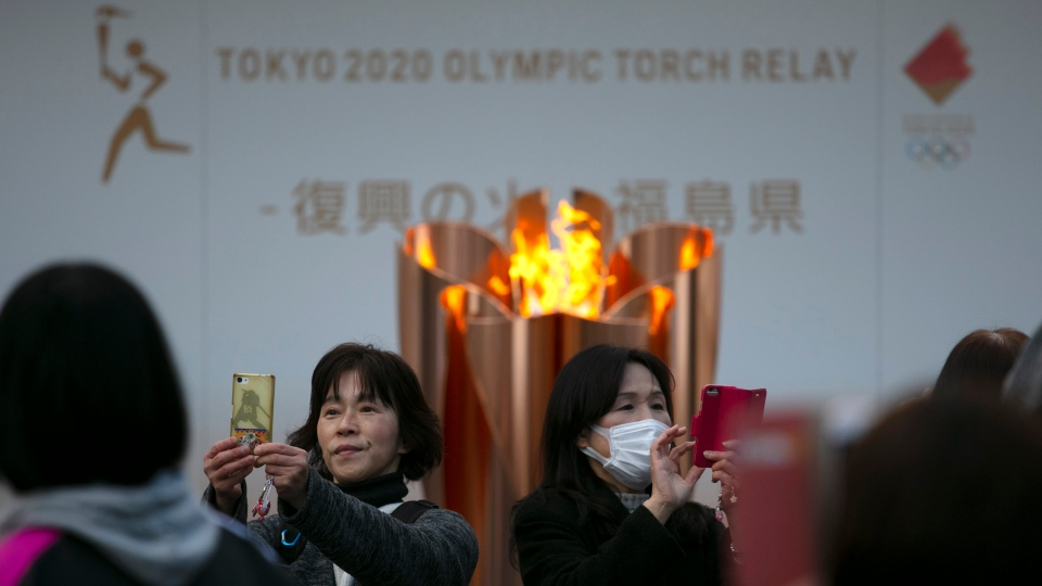 In this March 24, 2020, file photo, people take pictures with the Olympic Flame during a ceremony in Fukushima City, Japan. (AP Photo/Jae C. Hong, File)
