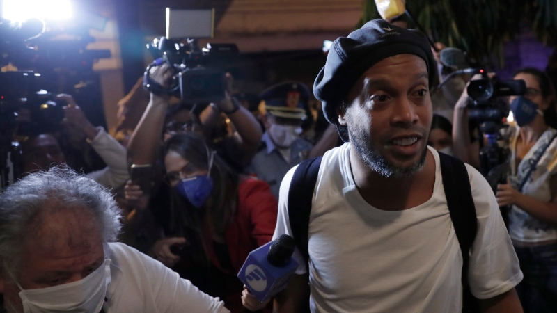 Surrounded by the media, former Brazilian soccer star Ronaldinho arrives at a hotel where he is to stay under house arrest in Asuncion, Paraguay, Tuesday, April 7, 2020. Ronaldinho and his brother Roberto De Assis Moreira spent a month in jail accused of entering Paraguay with fake passports. (AP Photo/Jorge Saenz)