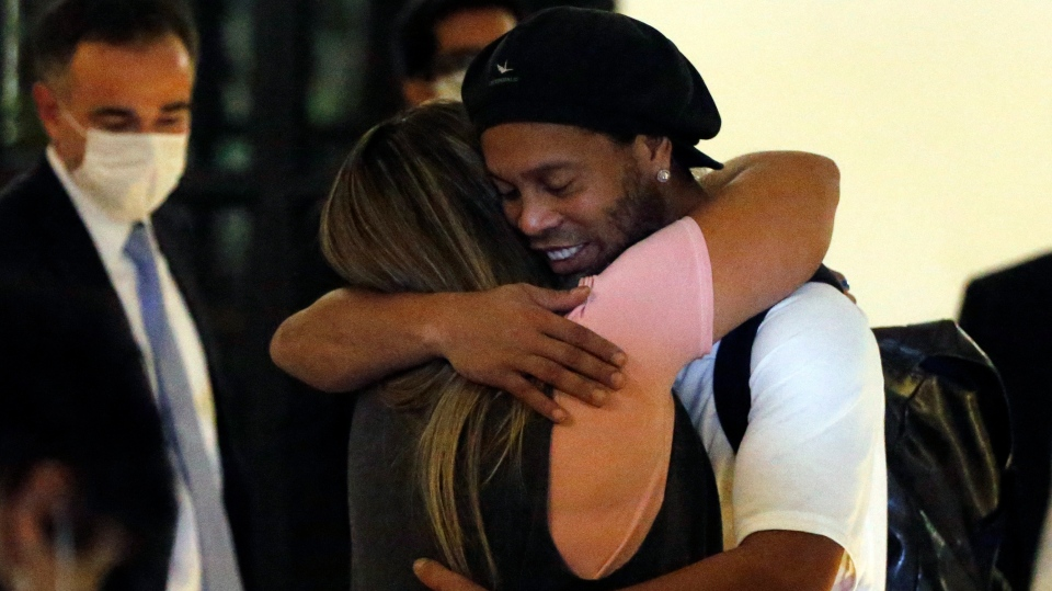 Former Brazilian soccer star Ronaldinho is embraced by a woman as he arrives at a hotel where he is to stay under house arrest in Asuncion, Paraguay, Tuesday, April 7, 2020. Ronaldinho and his brother Roberto De Assis Moreira spent a month in jail accused of entering Paraguay with fake passports. (AP Photo/Jorge Saenz)