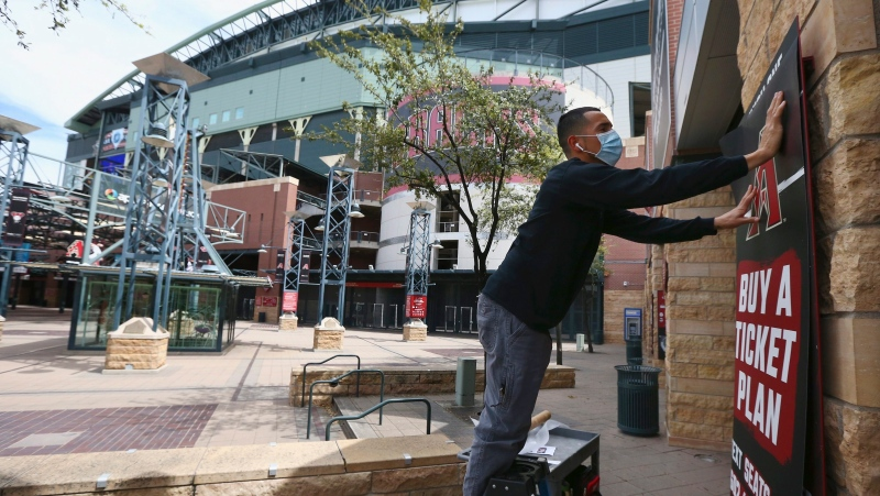 Joey Rodriguez, of Image Craft, installs an advertising banner in front of Chase Field Thursday, March 26, 2020, in Phoenix. The Arizona Diamondbacks would have hosted the Atlanta Braves in their season-opening baseball game Thursday, but the start of the MLB regular season is indefinitely on hold because of the coronavirus pandemic. (AP Photo/Ross D. Franklin)