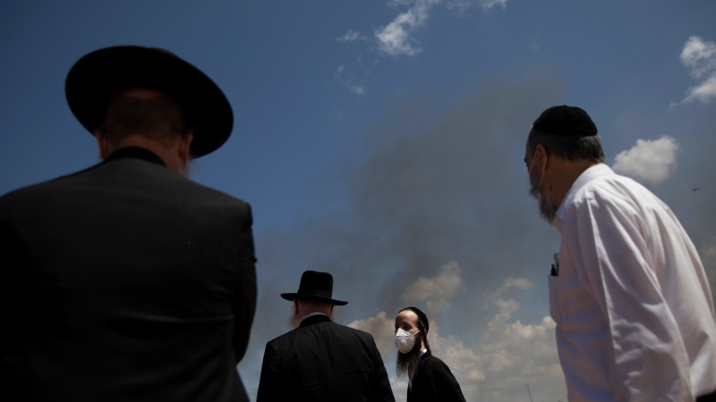 Ultra-Orthodox Jews wears face masks as Bnei Brak municipality burns a pile of leavened items collected from across the city in final preparation for the Passover holiday, following the government's measures to help stop the spread of the coronavirus, in Bnei Brak, Israel, Wednesday, April 8, 2020. (AP Photo/Oded Balilty)