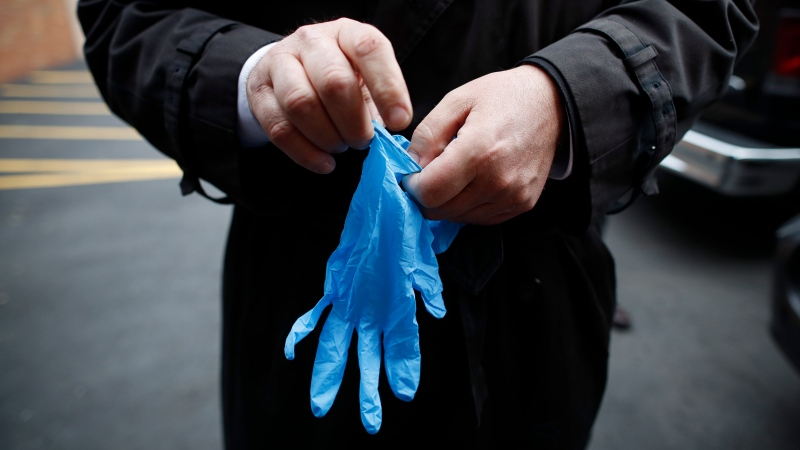 Funeral director Tom Cheeseman puts on protective gloves due to COVID-19 concerns as he delivers a body to a funeral home, Friday, April 3, 2020, in the Brooklyn borough of New York. (AP Photo/John Minchillo)