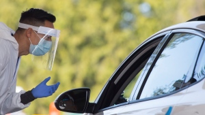 A Fraser Health healthcare worker speaks to a patient at a drive-through COVID-19 testing facility in Burnaby, B.C., Monday, April 6, 2020. (THE CANADIAN PRESS / Jonathan Hayward)