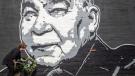 Maribeth Schmitt, of Lexington, Ky., places a wreath below a mural of singer John Prine in Lexington, Ky., on April 8, 2020. (Ryan C. Hermens / Lexington Herald-Leader via AP)