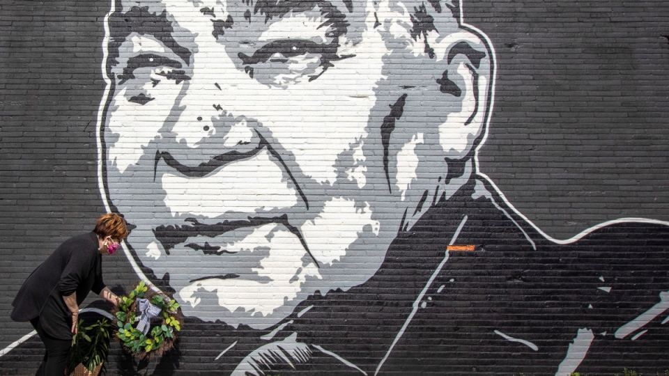 Maribeth Schmitt, of Lexington, Ky., places a wreath below a mural of singer John Prine in Lexington, Ky., on April 8, 2020. (Ryan C. Hermens / Lexington Herald-Leader via AP)
