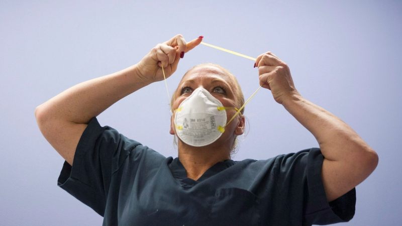 A healthcare professional removes her mask during a demonstration of Personal Protective Equipment (PPE) procedures at Toronto Western Hospital on Friday October 17, 2014.THE CANADIAN PRESS/Chris Young
