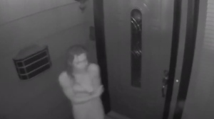 The video shows an unidentified woman wrapped in a towel frantically banging on the front door of a house. The woman is heard sobbing and repeatedly calling for help.