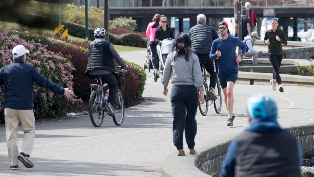 People run, bike and walk along the seawall in False Creek in Vancouver, Monday, April 6, 2020. THE CANADIAN PRESS/Jonathan Hayward