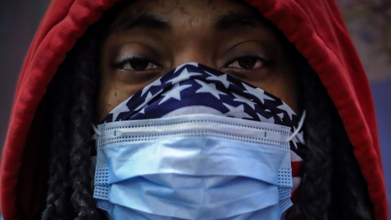 In this April 7, 2020, photo, a subway rider wears a mask and a bandana to protect himself against COVID-19 in New York. As the coronavirus tightened its grip across the country, it is cutting a particularly devastating swath through an already vulnerable population, black Americans. (AP / Bebeto Matthews)
