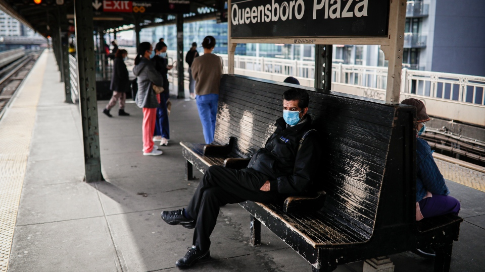 Riders, some wearing face masks due to COVID-19 concerns, wait for a subway train at Queensboro Plaza, Tuesday, April 7, 2020, in the Long Island City neighborhood in the Queens borough of New York. (AP Photo/John Minchillo)