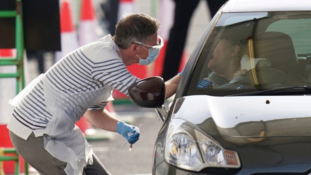 NHS worker is tested for Covid-19 at a drive-through testing centre in Manchester, England, on April 9, 2020. (Jon Super / AP)