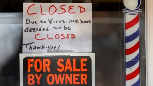 'For Sale By Owner' and 'Closed Due to Virus' signs are displayed in the window of Images On Mack in Grosse Pointe Woods, Mich., on April 2, 2020. (Paul Sancya / AP)
