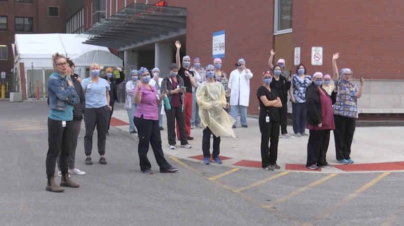 Nurses and hospital staff from St. Thomas Elgin General Hospital in Elgin County, Ont., are seen on April 8, 2020, standing outside the building and waving to farmers as a convoy of tractors drives by.