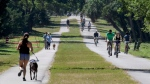 Runners, walkers and cyclists enjoy a section of the Pinellas Trail north of downtown Dunedin, Fla., Friday, March 27, 2020. (Douglas R. Clifford/Tampa Bay Times via AP)