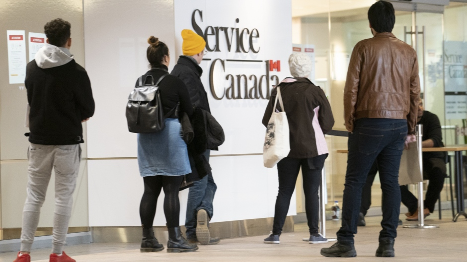 People line up at a Service Canada office in Montreal on Thursday, March 19, 2020. Statistics Canada says the economy lost 1,011,000 jobs in March as the COVID-19 crisis began to take hold. THE CANADIAN PRESS/Paul Chiasson