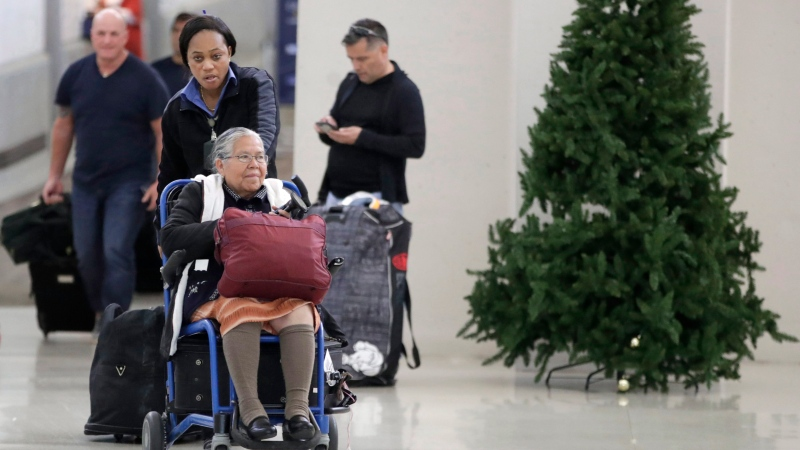 An employee pushes a woman on a wheelchair out of the international arrivals area on Terminal B at Newark Liberty International Airport, Tuesday, Nov. 21, 2017, in Newark, N.J. (AP Photo/Julio Cortez)