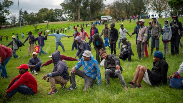 Homeless recyclers and other destitute people, some of whom said they have not eaten in three days practise limited social distancing as they lineup in a Johannesburg park, waiting to receive food baskets from private donors, on April 9, 2020. (Jerome Delay / AP)