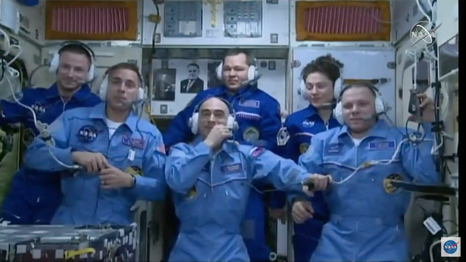 In this image from video made available by NASA, newly-arrived International Space Station crew members, foreground from left, Chris Cassidy, Anatoly Ivanishin and Ivan Vagner, stand with outgoing crew members, background from left, Andrew Morgan, Oleg Skripochka, and Jessica Meir during a news conference on Thursday, April 9, 2020. (NASA via AP)