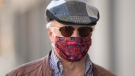 Paul Pedersen wears a mask quilted by his wife as he walks along the street in Ottawa, Monday April 6, 2020. (Adrian Wyld/THE CANADIAN PRESS)