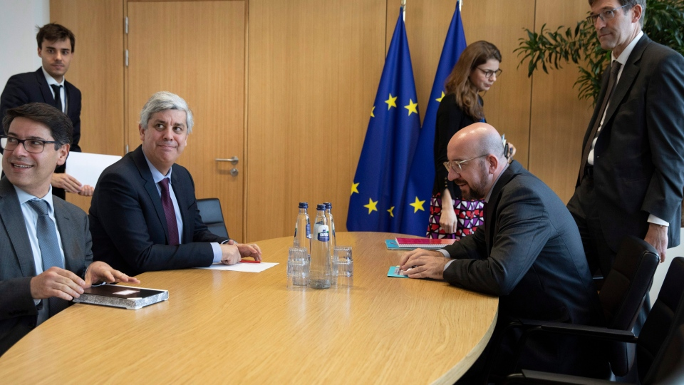 Eurogroup President and Portugal's Finance Minister Mario Centeno, third left, meets with European Council President Charles Michel, second right, at the Europa building in Brussels, Tuesday, Feb. 18, 2020. (AP Photo/Virginia Mayo, Pool)