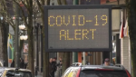 A COVID-19 alert sign is seen in Vancouver in this file photo.