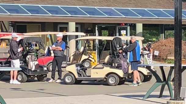 Golfers chat while maintaining their distance at the Newlands Golf and Country Club in Langley, B.C.