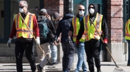 People wear protective face masks as they clean the sidewalks and streets in Vancouver's downtown eastside, Tuesday, April 7, 2020. THE CANADIAN PRESS/Jonathan Hayward