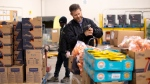 Neil Hetherington, CEO of The Daily Bread Food Bank sorts through groceries in Toronto on Wednesday March 18, 2020. THE CANADIAN PRESS/Chris Young