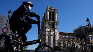 A man wearing a face mask rides his bike in front of Notre Dame cathedral during a nationwide confinement to counter the COVID-19, in Paris, Sunday, April 5, 2020. (AP Photo/Christophe Ena)