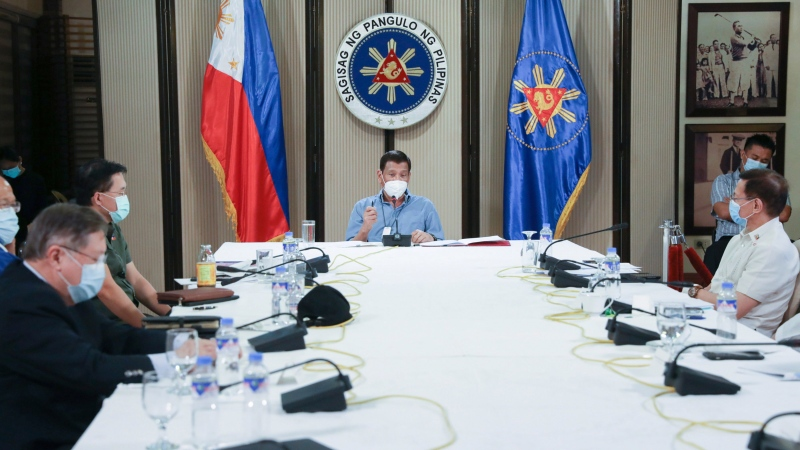 In this April 8, 2020, photo Philippine President Rodrigo Duterte, center, wears a protective mask as he meets with other government officials on the coronavirus situation of the country during a late night live broadcast from Malacanang, Manila. (Toto Lozano, Malacanang Presidential Photographers Division via AP)