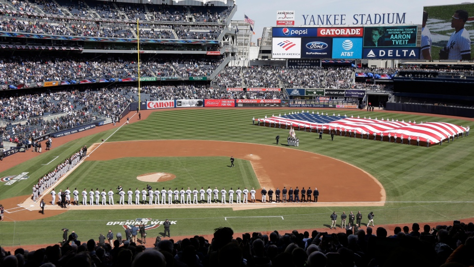In this March 28, 2019, file photo, a large flag is unfurled during the national anthem before an opening day baseball game between the New York Yankees and the Baltimore Orioles at Yankee Stadium in New York. (AP Photo/Seth Wenig, File)