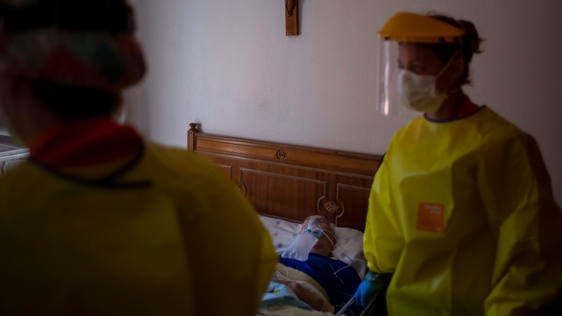 Medical workers making an emergency home visit walk away from a man, moments after they confirmed he died of severe respiratory problems in Barcelona, Spain, April 6, 2020. (AP Photo/Emilio Morenatti)