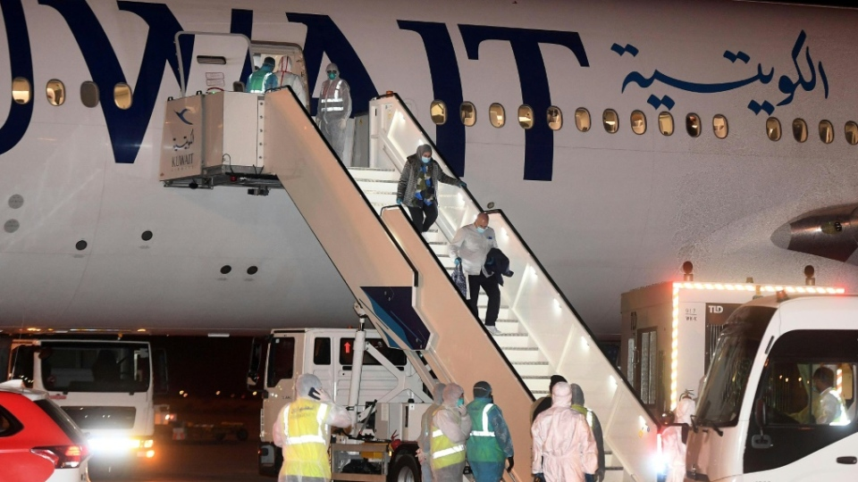 Kuwaitis returning home from Frankfurt are met by health workers in decontamination suits late last month. (AFP)