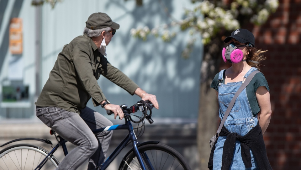 A woman wearing a P100 respirator amid concerns about COVID-19, crosses a street in the Downtown Eastside of Vancouver, on Friday, April 10, 2020. THE CANADIAN PRESS/Darryl Dyck
